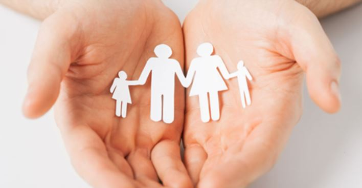 A par of human hands holding what appears to be a paper cut out of a family holding hands
