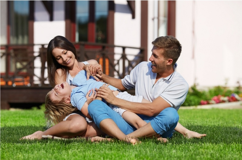 A Happy family of 3 playing on the grass